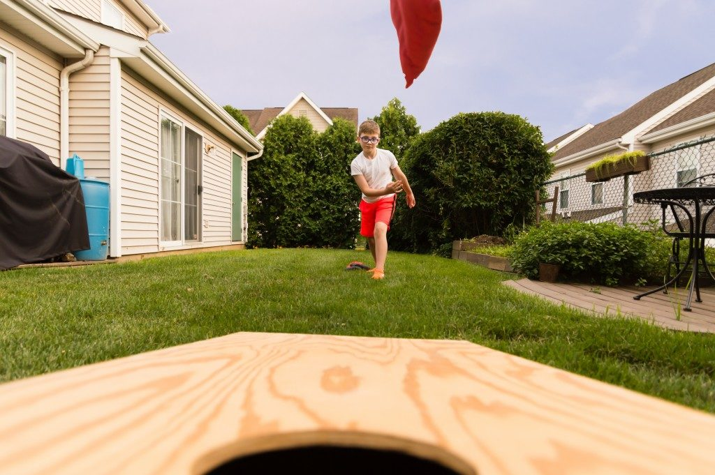 kid playing cornhole outdoors