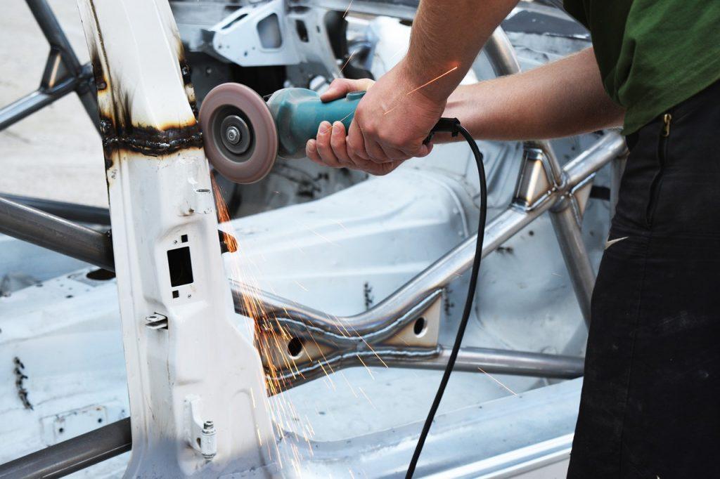 man welding a car door